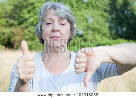 Old age woman showing thumbs up and down