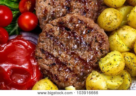 Close up Fresh juicy grill burgers served with ketchup young potatoes tomatoes and vegetables. On wo
