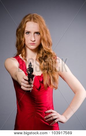 Girl in red dress with handgun against gray