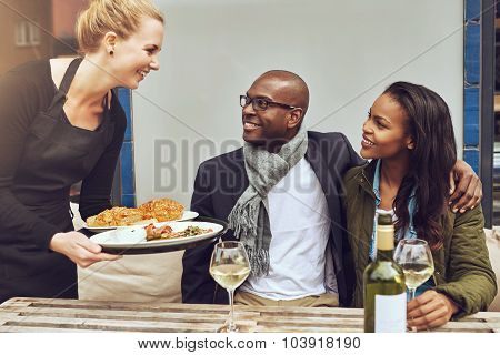 Waitress Serving An African American Couple Dinner