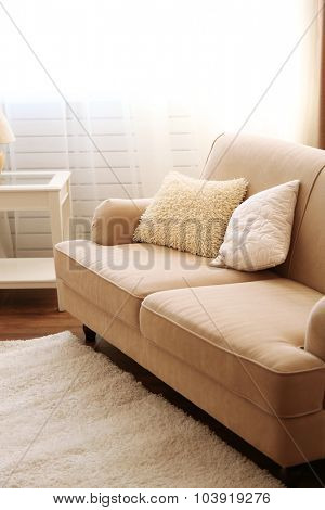 Creamy cozy sofa in the room