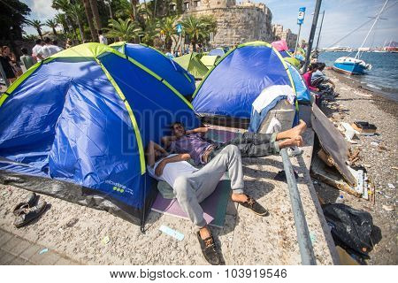 KOS, GREECE - SEP 28, 2015: Unidentified war refugees near tents. More than half are migrants from Syria, but there are refugees from other countries -Afghanistan, Pakistan, Iraq, Iran, Mali, Eritrea.