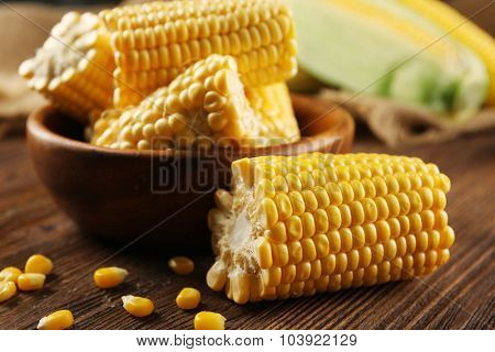 Ripe corn in bowl on wooden background