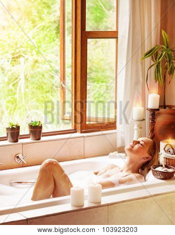 Happy woman bathing, lying down in bath tub with closed eyes of pleasure, relaxing in luxury spa resort, healthy lifestyle