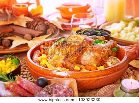 Tasty crispy chicken with baked vegetables on the centerpiece of table, family dinner in Thanksgiving day, traditional American holiday