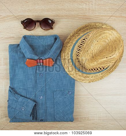 Top view collection of summer male clothing on the wooden background