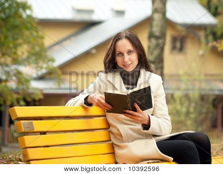 young woman reading book in park