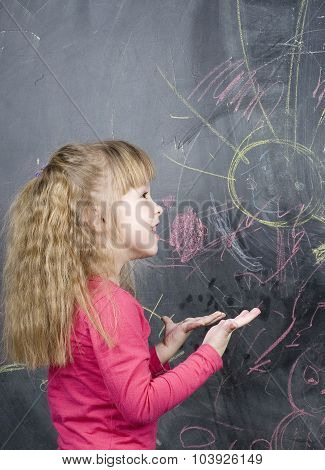 little cute girl in classroom at blackboard writing