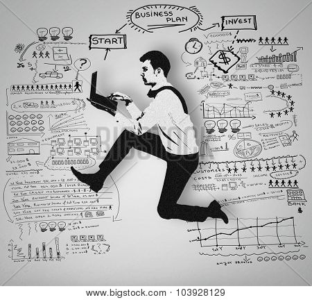 Man using computer and business plan on wall