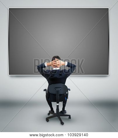 Young business man looking at something on wall