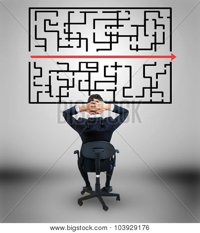 Young business man looking at maze solution