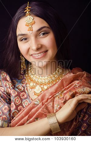 beauty sweet real indian girl in sari smiling on black background close up inosent