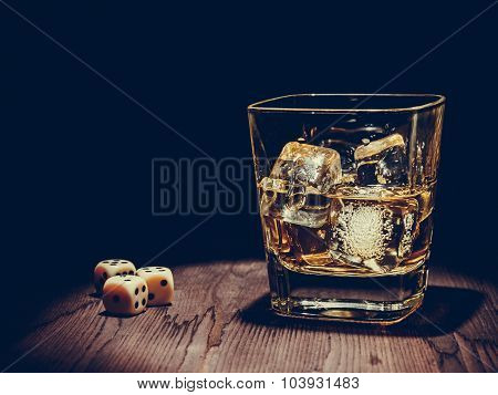 Dice Near Whiskey Glass On Old Wood Table, Concept Of Game