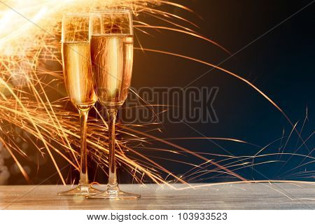 champagne glasses with fire on black background. Blue and gold flare at background
