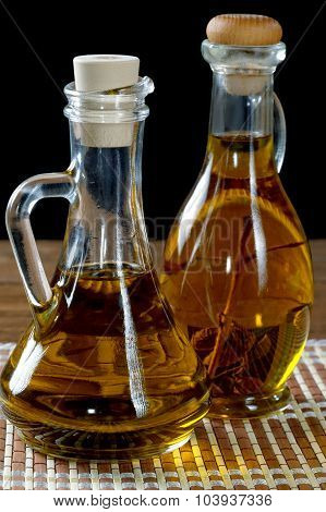 Two Bottles Of Olive Oil On Rustic Table