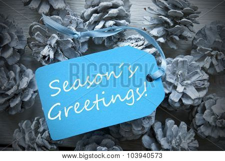 Light Blue Label On Fir Cones With Seasons Greetings