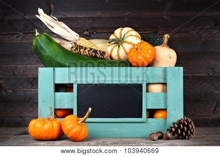 Harvest crate with autumn vegetables against dark wood
