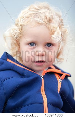 Little boy with blue sport jacket looking at camera