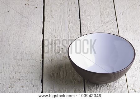 Brown And White Salad Bowl On White Boards.