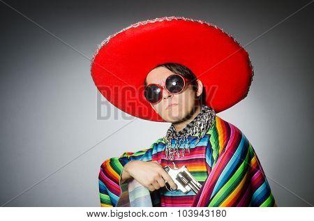 Man in vivid mexican poncho holding handgun against gray
