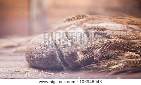 Bread and wheat on wooden table, shallow DOF, raw image. Header for website