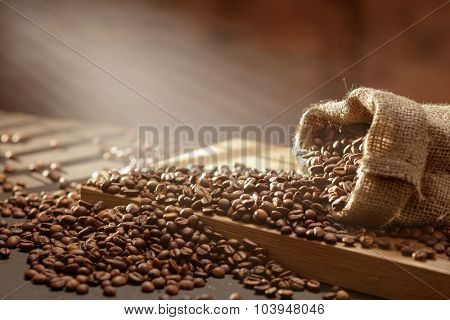 spilled coffee beans in bag on wooden table. Morning light