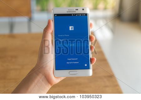 Loei, Thailand - August 7, 2015: Hand holding samsung galaxy note edge with mobile application for Facebook on the screen