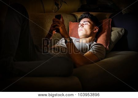 Young Man on Sofa Lit by Light from Cell Phone