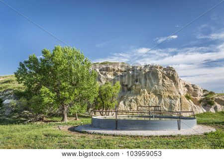 cattle water tank and rock cliff,  Pawnee National Grassland in northern Colorado