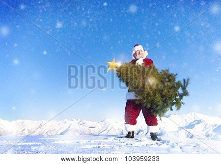 Santa claus carrying christmas tree on snow covered mountain.