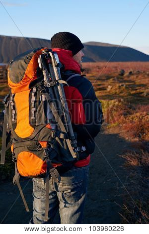 Hiking man outdoors with backpack and tripod to take nature landscape photographs