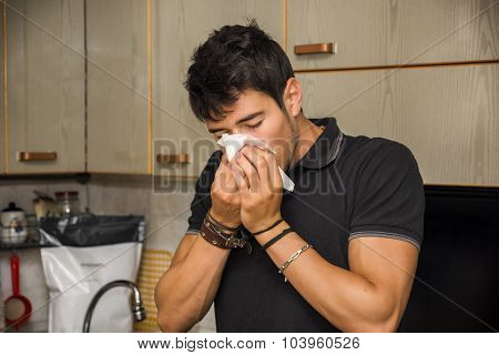 Young Man Blowing Nose into Tissue