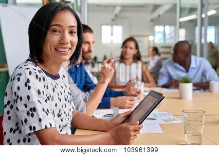 portrait of professional business woman during coworkers boardroom meeting with tablet computer taking notes
