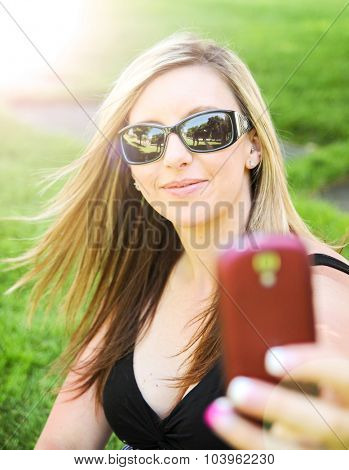 a cute girl smiling at the camera while taking a selfie (self portrait)