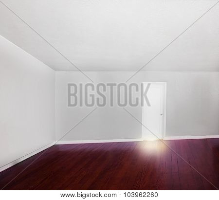 a big empty white room with a hard wood stained floor and light leaking from under the closed door