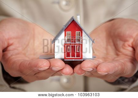 Hands with little house. Real estate and construction background.