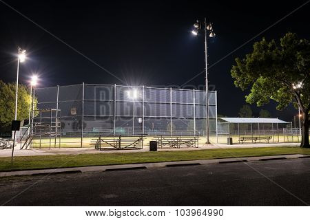 Empty Baseball Field With The Lights On At Night