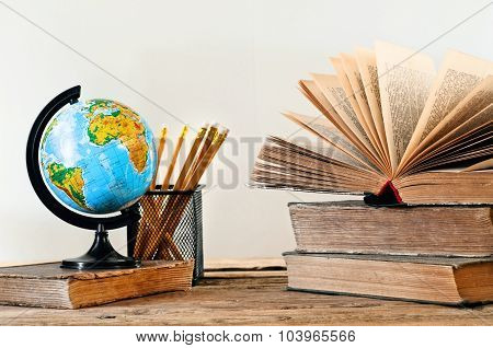Stack Of Books With A Globe And Pencil