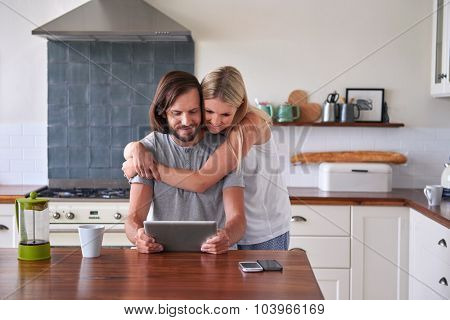 couple bonding and enjoying tablet computer in home kitchen