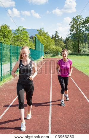Two Women Running On Track Together