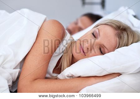 peaceful young couple sleeping comfortably with alarm clock in bed at home