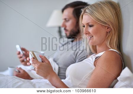 young couple with mobile cell phone sending emails working from bed