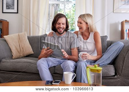 smiling couple with tablet computer coffee mug on sofa couch at home