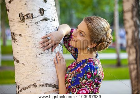 Portrait of Beautiful blond woman on a tree in autumn park