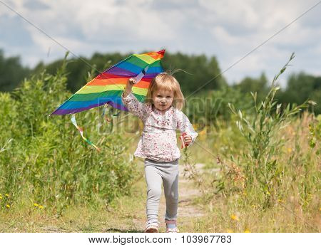 little cute girl flying a kite in a meadow on a sunny day. close-up