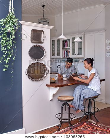 Modern lifestyle with technology, couple with coffee tablet mobile cellphone in home kitchen having breakfast