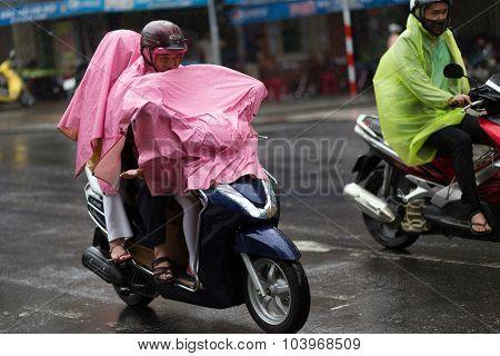 DA NANG, VIETNAM, DECEMBER 14, 2015: Vietnamese people riding motorbike under a heavy rain, full covered with raincoat in Da nang, Vietnam