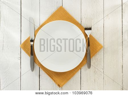 cloth napkin and plate on wooden background