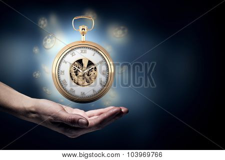 Close up image of human hand holding pocket watch