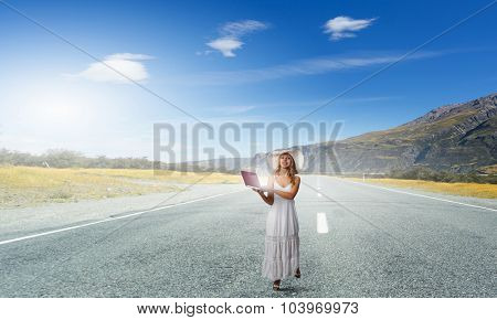 Young lady in white dress and hat outdoor with laptop in hands